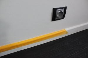 Adhesif Perfect : pose de l'adhésif sur une plinthe en bois