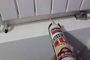 Application de la colle acrylique blanche entre le coffrage et le mur