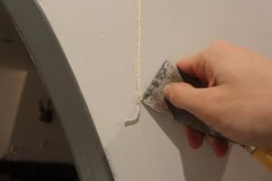 Élargir la fissure à l'aide d'un grattoir ou couteau à enduire puis dépoussiérer.
